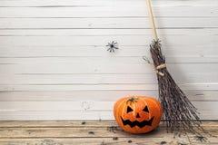 Potirons de Halloween avec les visages peints et balai du ` s de sorcière sur un courtiser photo stock