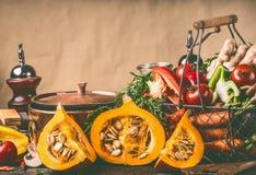 Potirons du Hokkaido sur la table de cuisine avec faire cuire le pot et les ingrédients au fond rustique de mur, vue de face Images stock