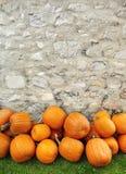Potirons empilés contre un mur en pierre rustique Photo stock