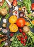 Potirons et ingrédients délicieux de légumes de récolte pour la cuisson savoureuse, préparation sur le fond rustique foncé Photo libre de droits