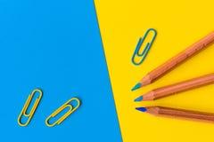 Potloden en paperclips tegen een blauwe en gele achtergrond Stock Foto