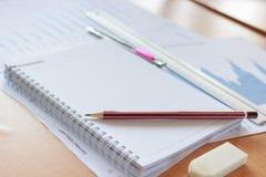 Potloden, notitieboekjes en grafiek in bureau Royalty-vrije Stock Afbeelding