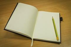 Potlood en notitieboekje met blanco pagina op bureaulijst Royalty-vrije Stock Afbeelding