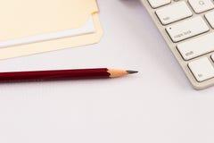 Potlood met toetsenbord en dossieromslag tegen een witte achtergrond Stock Foto's