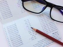 Potlood, oogglazen en spaarrekeningbankboekje of financiële staat op witte achtergrond Royalty-vrije Stock Fotografie