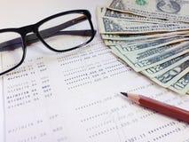 Potlood, oogglazen, geld en spaarrekeningbankboekje of financiële staat op witte achtergrond Royalty-vrije Stock Afbeeldingen