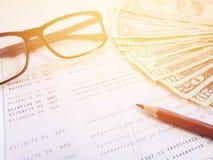 Potlood, oogglazen, geld en spaarrekeningbankboekje of financiële staat op witte achtergrond Stock Foto's