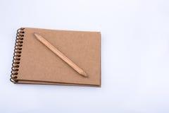 Potlood op een notitieboekje op witte achtergrond wordt geplaatst die Stock Afbeeldingen