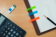 Potlood, post-itdocument, calculator, usb en boek op houten lijst Stock Foto's