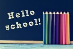 Potloodkleurpotloden en tekst hello school op een bord wordt geschreven dat Stock Fotografie