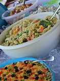 Potluck Picnic Food. Taco dip, pasta salad, potato salad on top of ice at a picnic Stock Photos