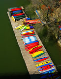 Potomac River Kayak Pier. Multiple and bright colors of the kayaks on a floating dock stand out along the green waters of the Potomac River at a boat house by Stock Images