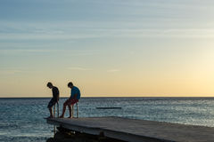PotoMaripeople на peir на заходе солнца - пристаньте взгляды к берегу Curacao Стоковые Фотографии RF