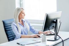 Potomstw, atrakcyjnej i ufnej kobieta pracuje w biurze, fotografia royalty free