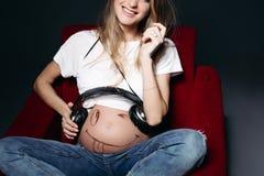 Potomstw ono uśmiecha się i trzyma ciężarne macierzyste słuchawki na jej brzuszku zdjęcie stock