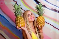 Potomstwa, śliczna, piękna szczupła blondynki kobieta z afrykanów warkoczami z ananasami w jej rękach i, Obrazy Stock