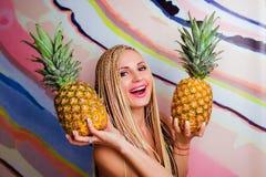 Potomstwa, śliczna, piękna szczupła blondynki kobieta z afrykanów warkoczami z ananasami w jej rękach i, Obraz Stock
