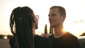 Potomstwa, atrakcyjnej pary słuchająca muzyka wraz z białymi słuchawkami Trwanie outside na ulicie, taniec, całowanie zbiory