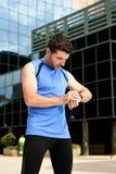 Potomstwa bawją się mężczyzna sprawdza czas na chrono zegarów biegaczów zegarka mienia bidonie po sesi szkoleniowa Zdjęcia Stock