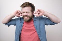 Potomstwa, brodaty mężczyzna zakrywają jego ucho z jego palcami i pokazują że no chce słuchać pojedynczy bia?e t?o fotografia royalty free