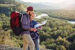 Potomstwa dobierają się podróżować wpólnie w górach Szczęśliwy modnisia mężczyzna i jego dziewczyna z plecakami planuje trasę obo obrazy stock