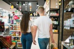 Potomstwa dobierają się w karmowym supermarkecie, tylny widok fotografia stock