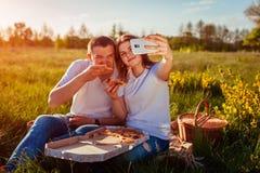 Potomstwa dobierają się łasowanie pizzę outside i bierze selfie Kobieta i mężczyzna ma pinkin przy zmierzchem Faceci ma zabawę obraz royalty free