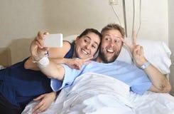 Potomstwa dobierają się brać selfie fotografię przy sala szpitalną z mężczyzna lying on the beach w kliniki łóżku Fotografia Stock