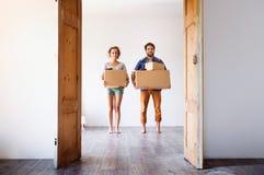 Potomstwa dobierają się chodzenie w nowym domu, mień pudełka Obrazy Stock