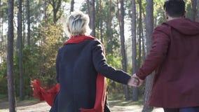Potomstwa dobierają się chwytów bieg w sosnowym lesie w promieniach słońce i ręki Facet i dziewczyna w przypadkowej odzieży wydaj zbiory wideo