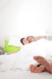 Potomstwa dobierają się cieszyć się relaksującego dzień w łóżku obraz stock