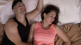 Potomstwa dobierają się cuddling on łaskocze ona i siedzieć w łóżku żartuje i śmia się zdjęcie wideo