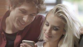 Potomstwa dobierają się dopatrywanie fotografie na telefonie komórkowym w nowożytnym loft wnętrzu zbiory