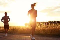 Potomstwa dobierają się jogging w suberbs po zmierzchu Fotografia Royalty Free