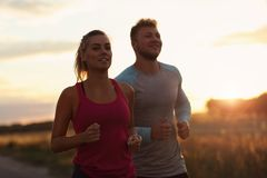 Potomstwa dobierają się jogging w suberbs po zmierzchu Zdjęcia Royalty Free