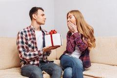 Potomstwa dobierają się, mężczyzna dają kobiecie prezentowi, siedzi na leżance w domu obraz royalty free