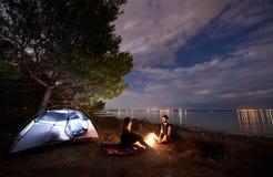 Potomstwa dobierają się mężczyzna i kobiety ma odpoczynek przy blisko lasu turystycznym namiotem i płonącym ogniskiem na dennym b zdjęcie stock