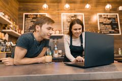 Potomstwa dobierają się mężczyzny i kobiety właścicieli małej nowożytnej kawy domowy używa laptop dla pracy zdjęcia royalty free