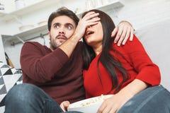 Potomstwa dobierają się mieć romantycznego evening w domu wpólnie ogląda strasznego film Zdjęcie Stock