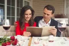Potomstwa dobierają się mieć romantycznego gościa restauracji w restauracyjnym mienie menu koncentrującym zdjęcie stock