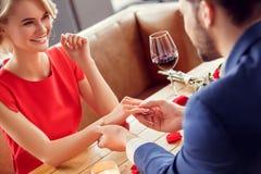 Potomstwa dobierają się na dacie w restauracyjnej obsiadanie mężczyzny mienia ręce jest ubranym propozycji ringowy rozochoconego  obraz stock
