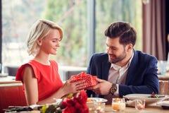 Potomstwa dobierają się na dacie w restauracyjnym obsiadanie mężczyźnie daje prezenta pudełku kobiety ono uśmiecha się szczęśliwy obrazy stock