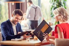 Potomstwa dobierają się na dacie w restauracyjnym siedzącym wybiera naczyniu od menu radosnego zdjęcie royalty free