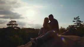 Potomstwa dobierają się na wierzchołku skała, przystojny młody kochanek tenderly dotykają jego dziewczyny w jaskrawym świetle sło zbiory