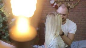 Potomstwa dobierają się obsiadanie na łóżku na tle choinka Świąteczny wieczór w domu Mężczyzna całuje kobiety zbiory wideo