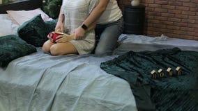 Potomstwa dobierają się obsiadanie na łóżku na tle choinka Świąteczny wieczór w domu Mężczyzna całuje kobiety zdjęcie wideo