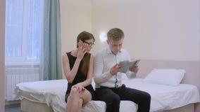 Potomstwa dobierają się obsiadanie na łóżku w żywym pokoju, mężczyzna powołania planistyczna wycieczka używać mapę, kobieta ma ro Zdjęcie Royalty Free