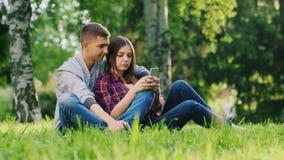 Potomstwa dobierają się odpoczywać wpólnie w parku, sztuka na twój telefonie, ono uśmiecha się zdjęcie wideo