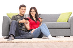 Potomstwa dobierają się pić wino sadzającego kanapą Zdjęcie Royalty Free