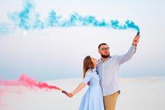 Potomstwa dobierają się pozycję na mienie barwiącej dymnej bombie, piasku, romantycznej parze z błękitnym kolorem i czerwonego ko Obrazy Royalty Free